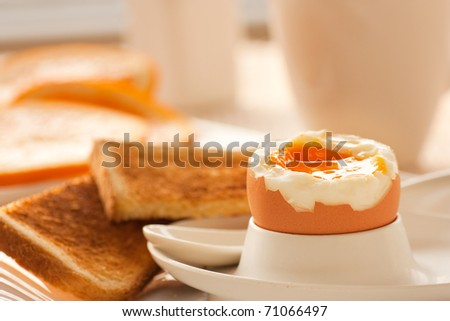 Soft boiled egg with toasted bread and slices of oranges in the back. Shallow depth of filed. - stock photo