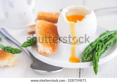 Soft boiled eggs with asparagus and toast soldiers - stock photo