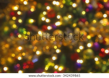 Soft bokeh Christmas Lights background.  Colours of rich warm amber, red, green, blue and purple - stock photo
