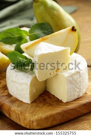 soft brie cheese (camembert) with pears on a wooden board - stock photo