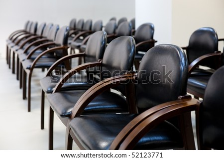 Soft chairs of black leather standing in row for seminar or business activities