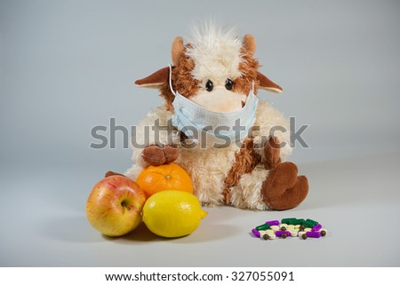 Soft children's toy bull in a medical mask with healthy fruits and various pills on a gray background                                - stock photo