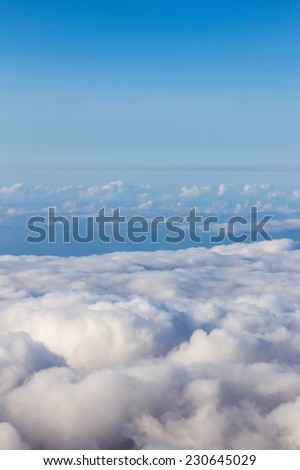 Soft clouds over view from airplane flying - stock photo