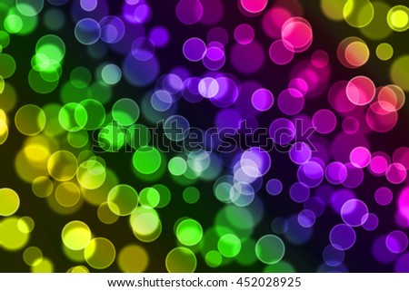 Soft colorful bokeh on black background. Defocused blurry circle lights. Mostly yellow, green, purple and red