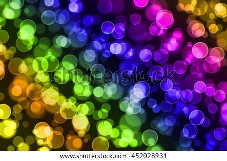 Soft colorful bokeh on black background. Many defocused blurry circle lights