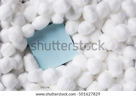 Soft cotton balls around a blank paper message. Carefree, softness, love message