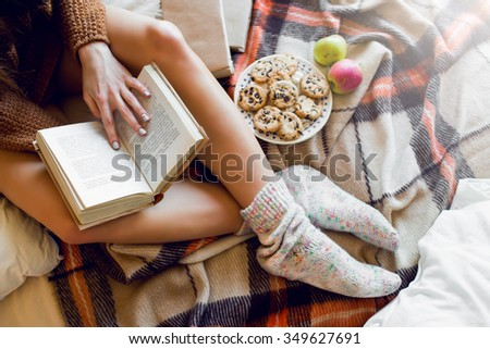 Soft cozy photo of slim tan woman in warm sweater on the bed with cup of tea in hands, top view point. Girl sitting on checkered plaid near old books and cookies. - stock photo