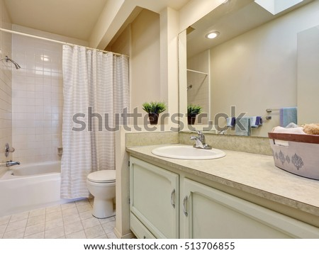 Soft creamy tones  bathroom with tile floor, bath and shower combo, toilet and bathroom vanity. Northwest, USA