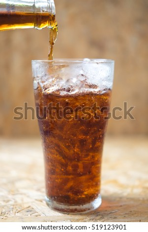soft drink being poured into glass with ice cubes