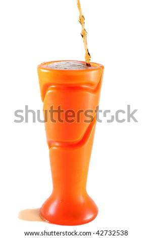 Soft drink or juice spilling out of an orange plastic vase - stock photo