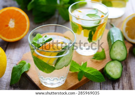 Soft drink with cucumber, orange,  lemon and mint - stock photo