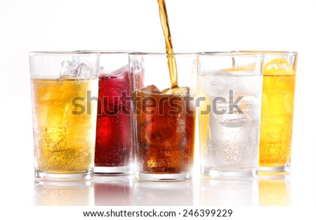 SOFT DRINKS - Soft drinks with ice being poured - stock photo