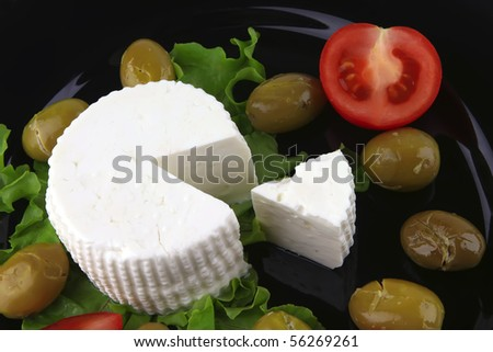 soft feta cheese on black dish with gold olives - stock photo