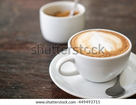 soft focus and out of focus latte coffee on wood table and granulated sugar background