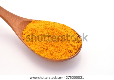 Soft focus and selective focus of Turmeric powder on the wooden spoon with white  background.