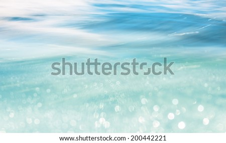 Soft focus bokeh light effects over a flowing ocean wave. - stock photo