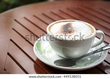 Soft focus cappuccino coffee on wood table and sunlight background in coffee shop