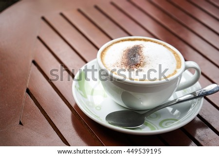 Soft focus cappuccino coffee on wood table background and sunlight background
