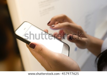 Soft focus finger woman hand touching blank of smart phone in blur store background.For and business financial concept ideas.