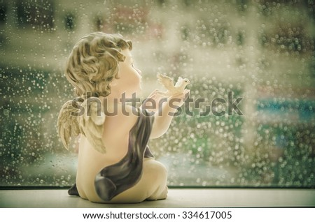 Soft focus for Little Cupid holding white dove resin in rain background with a retro vintage. - stock photo