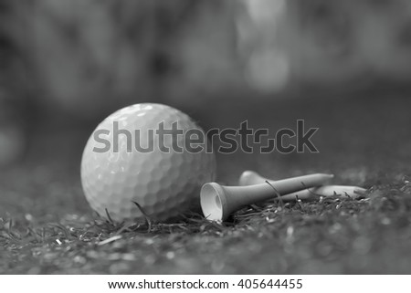 Soft focus golf ball and tee in black and white tone. - stock photo