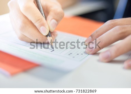 soft focus.high school or university student holding pencil writing on paper answer sheet.sitting on lecture chair taking final exam attending in examination room or classroom.