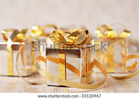 Soft focus holiday background with tiny sterling silver giftbox ornaments and gold ribbon.  Macro with extremely shallow dof. - stock photo
