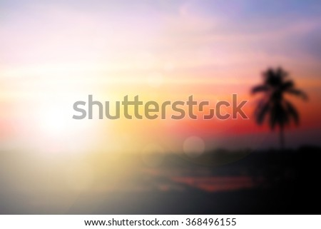 Soft focus image field during sunrise. Abstract blur colorful background of blurred colorful Sunset sky with silhouette coconut tree. Vacation summer. Nature wallpaper of sunset. Orange and clouds. - stock photo
