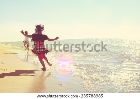 Soft focus kids running at the beach.  Instagram effect - stock photo