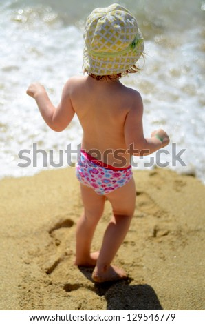 Soft Focus Lifestyle Image Of A Young Child Playing On A Sunny Beach - stock photo