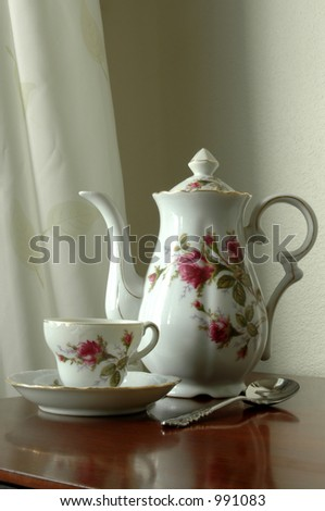 soft focus of antique teapot and teacup sitting on old teacart - stock photo