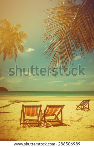 soft focus of coconut tree and beach wooden bed on white sand with beautiful blue sea over clear blue sky. vintage color tone.Koh Kood island Trat Province, Thailand.