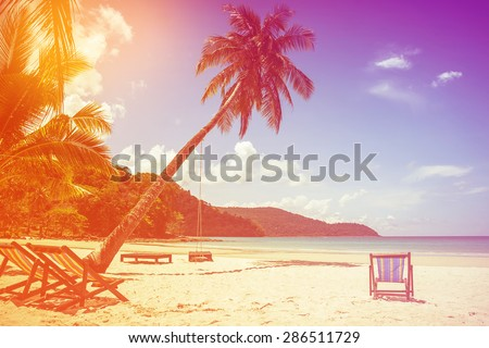 soft focus of coconut tree and beach wooden bed on white sand with beautiful blue sea over clear blue sky. vintage color tone. Koh Kood island Trat Province, Thailand. - stock photo