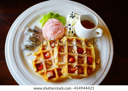 Soft focus of delicious Waffles with dragon fruit, strawberry, green apple with ice cream and honey on white plate (natural light in the cafe) - stock photo