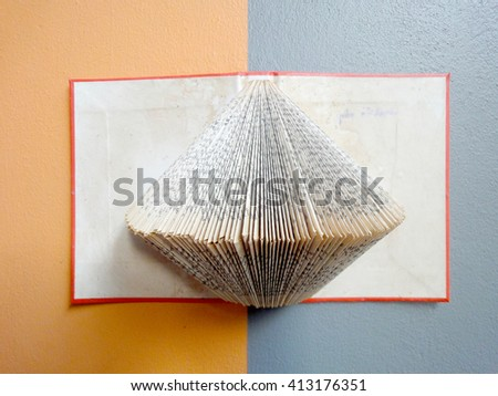 soft focus of old book with folded pages. Old Book folding is design very classic on the two tone with orange and  grey wall. still life style - stock photo