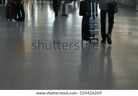 Soft focus of traveler walking with trolley bag