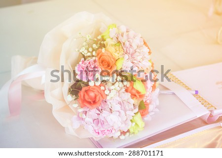 soft focus of wedding bouquet with notebook ,vintage color tone. - stock photo