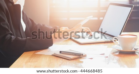soft focus of woman hand working and smart phone and laptop on wooden desk in office  morning light. vintage effect