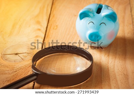 soft focus photo of blue piggy bank on wooden floor with magnifying glass on morning sunlight. vintage color tone. - stock photo