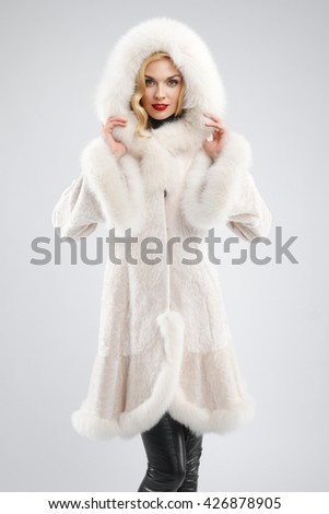 Soft focus portrait of attractive lady in white fur coat with hood on head. Perfect makeup, red mat lips and blue eyes - stock photo