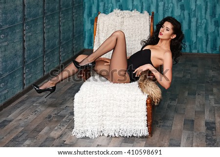 Soft focus portrait of caucasian model in black body and black pantyhose plays with legs on armchair. Wide open aperture, film grain. - stock photo