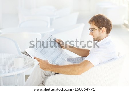 soft focus portrait of man reading a newspaper (focus on his eyes)