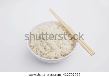 Soft focus Thai rice in white bowl and chopsticks on white background/ top view. - stock photo
