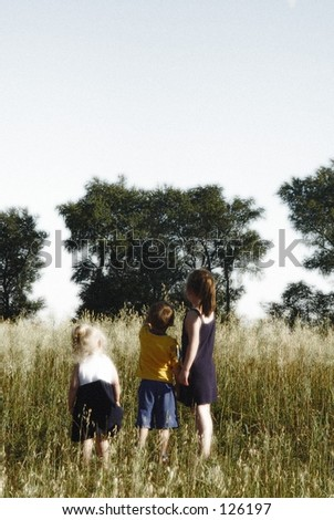 Soft focus three children in misty field.  Room for copy. - stock photo