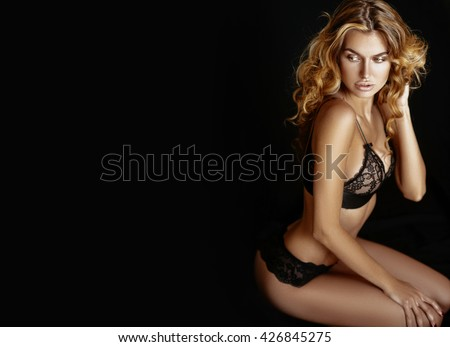 Soft focus. Very beautiful woman model with long blonde curly hair and makeup. Posing on a black background in black lace underwear and a black jacket. - stock photo