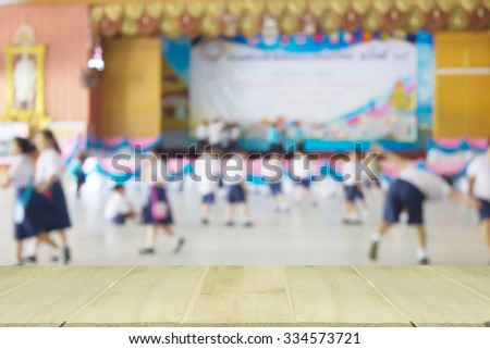 soft focus wooden table with blur of student playing  in school - stock photo