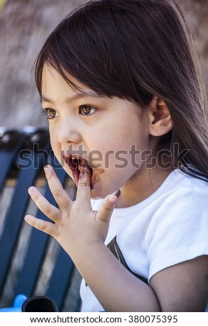 Soft focused filter colored and closed up a little girl tasting eating chocolate and bread sticks on metal bench at public park
