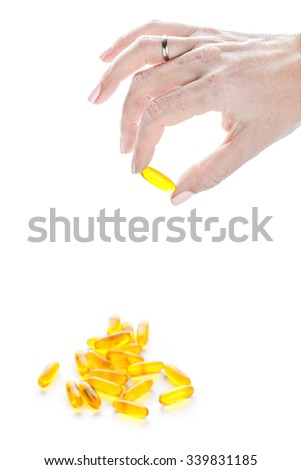 Soft gels pills with Omega-3 oil in fingers closeup on white background - stock photo