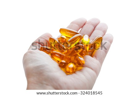 Soft gels pills with Omega-3 oil in hand closeup on white background - stock photo
