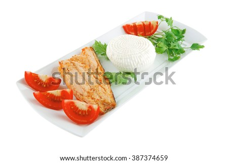 soft goat feta salt cheese with grilled sea salmon tomatoes and green lettuce salad served on white china plate isolated on white background - stock photo